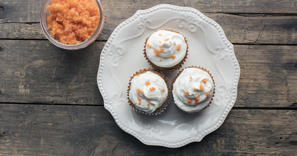 three cupcakes on a white plate next to carrot juice pulp