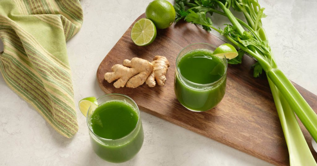 two glasses of celery juice with ingredients on a cutting board