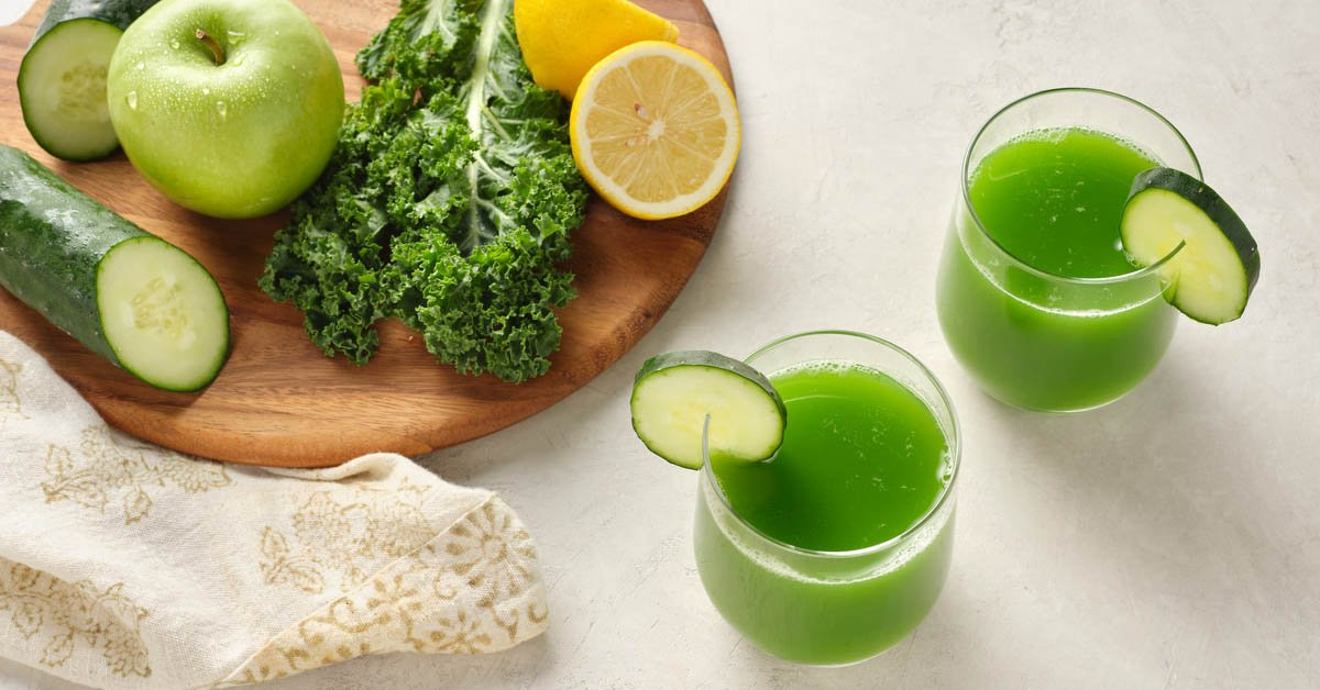 two glasses of green juice surrounded by ingredients