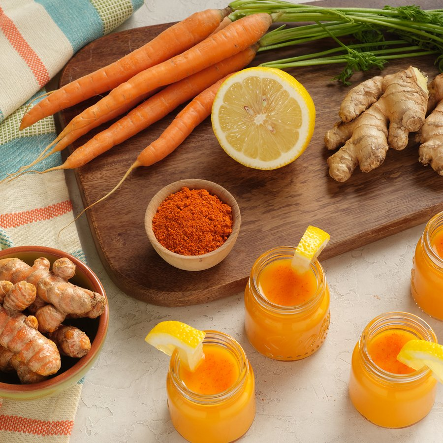 juice shots surrounded by the ingredients carrot, lemon, ginger, and turmeric to make this cold press wellness shot recipe