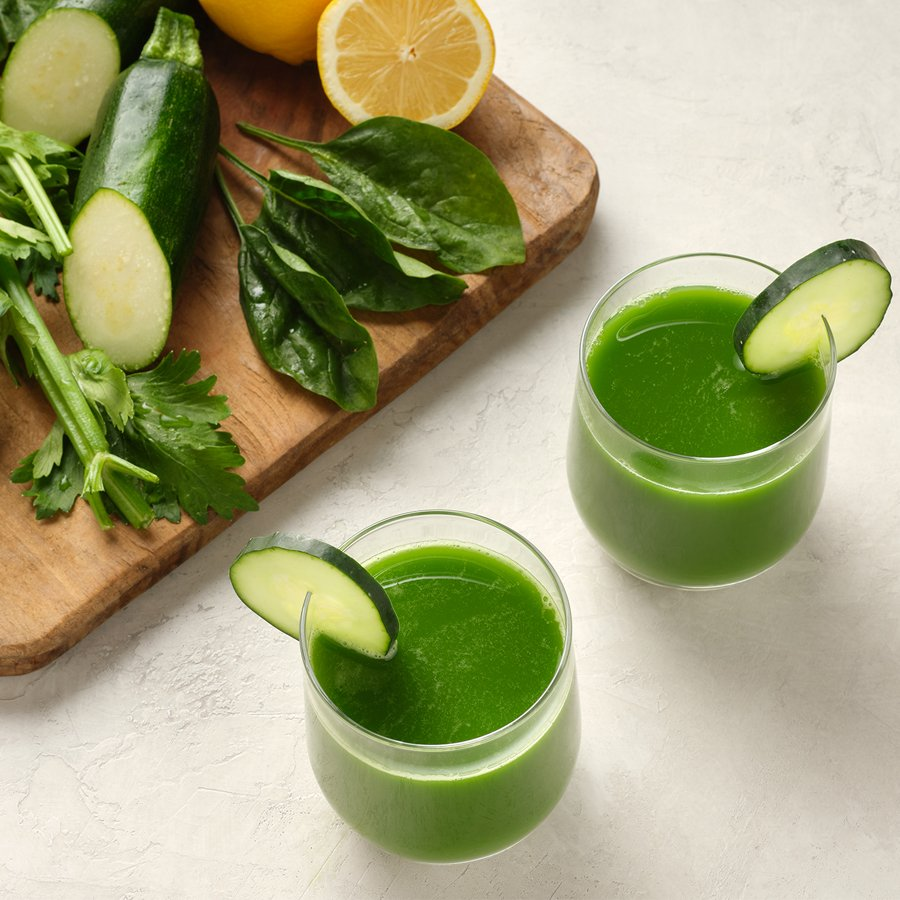two glasses of green juice surrounded by ingredients cucumber, spinach, romaine, zucchini, celery, lemon, and water cress on a neutral surface