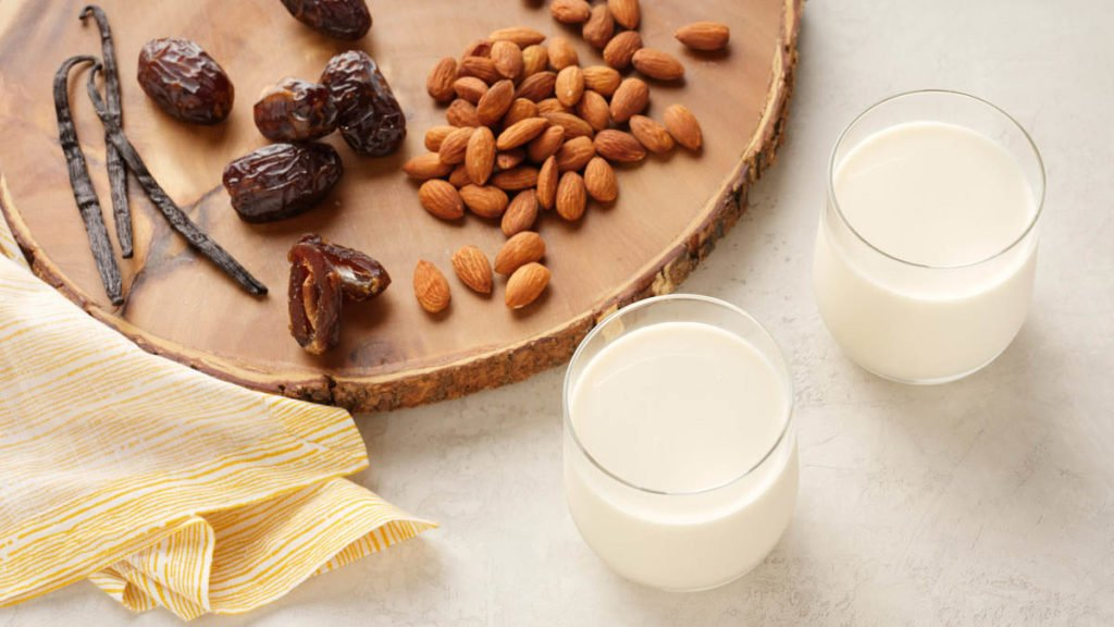 two glasses of cold pressed almond milk surrounded by dates, vanilla and almonds on a wood cutting board.