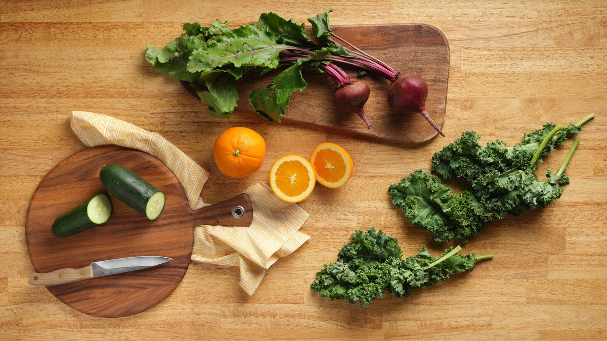 beets, oranges, cucumber and kale on a wood cutting board