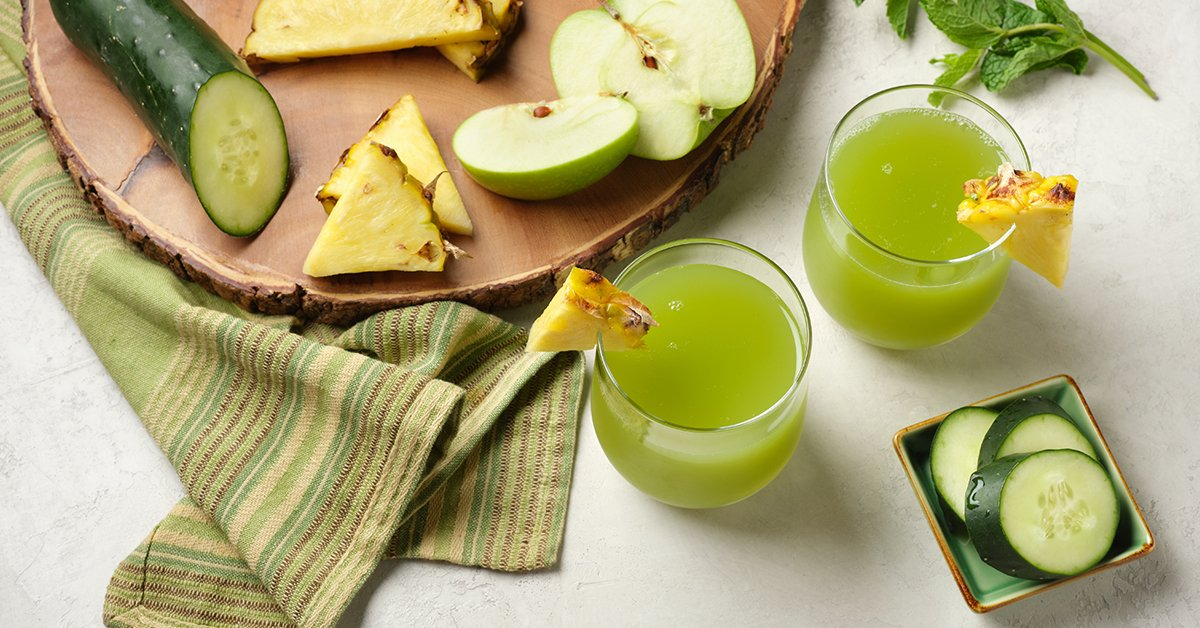two glasses of cold pressed green juice made with mint, pineapple, green apple and cucumber on a wooden cutting board