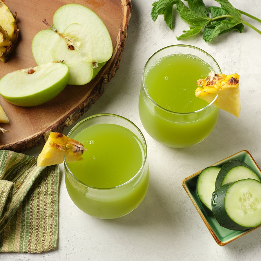two glasses of cold pressed green juice made with mint, pineapple, green apple and cucumber on a white surface