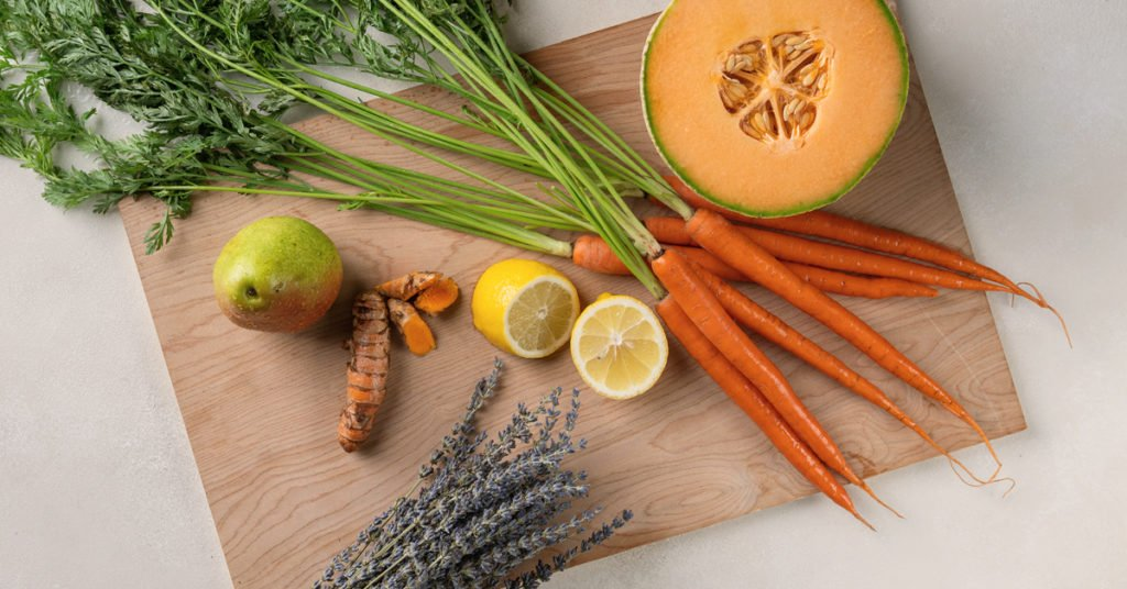 ingredients for cantaloupe melon juice recipe with carrots, lemon, turmeric, pear and lavender