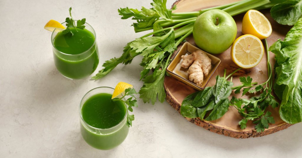 two glasses of green juice with the ingredients, spinach, celery, green apple, ginger, lemon and parsley on a wood cutting board