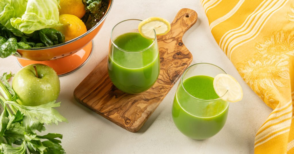 two glasses of green cabbage juice on a wooden cutting board