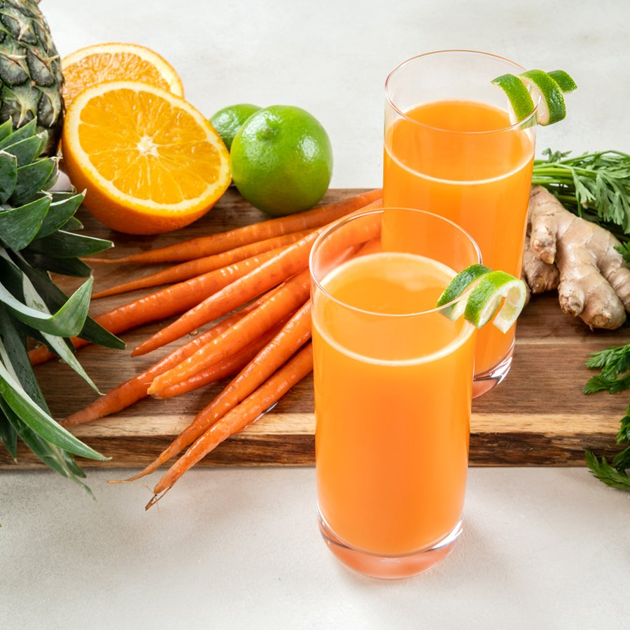 carrot orange pineapple juice glasses on a table next to ingredients