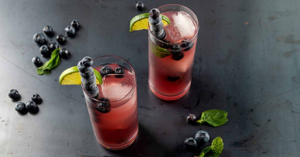cold pressed cocktail blueberry mojito on a steel surface